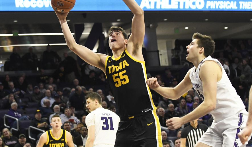 Iowa center Luka Garza (55) shoots as Northwestern center Ryan Young (15) defends during the first half of an NCAA college basketball game Tuesday, Jan. 14, 2020, in Evanston, Ill. (AP Photo/David Banks)