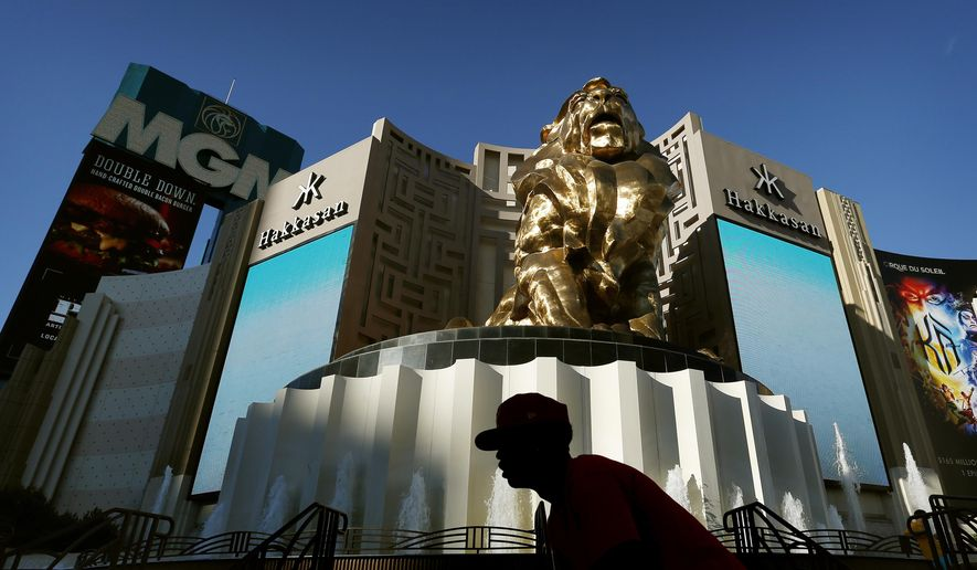 In this Aug. 3, 2015, file photo, a man rides his bike past the MGM Grand hotel and casino in Las Vegas. (AP Photo/John Locher, File)