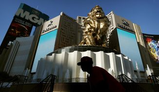 FILE - In this Aug. 3, 2015, file photo, a man rides his bike past the MGM Grand hotel and casino in Las Vegas. MGM Resorts International is selling the MGM Grand and Mandalay Bay resorts and casinos on the Las Vegas Strip to a joint venture for about $2.5 billion. (AP Photo/John Locher, File)