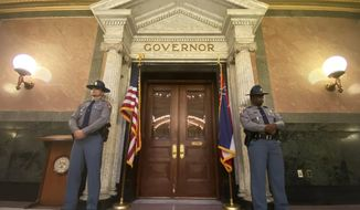 Guards stand watch outside the Governor's executive office before the start of the gubernatorial inauguration ceremony for Tate Reeves at the Capitol in Jackson, Miss. Tuesday, Jan. 14, 2020.  (Cam Bonelli/The Clarion-Ledger via AP)