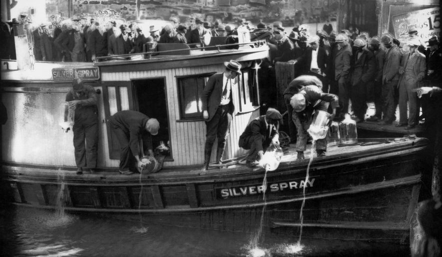 "In this 1922 file photo spectators gather by the side of captured rum runner, Silver Spray, as they watch prohibition agents pour ""white lightning"" from the five-gallon bottles on the deck into the Elizabeth River, Norfolk, Va. The Prohibition Era, which lasted from Jan. 17, 1920, until December 1933, is now viewed as a failed experiment that glamorized illegal drinking. (Charles S. Borjes/The Virginian-Pilot via AP) **FILE**"