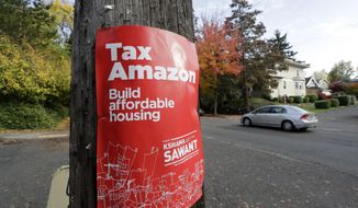 """FILE - In this Oct. 23, 2019, file photo, a campaign poster for Seattle City Council incumbent candidate Kshama Sawant is posted outside her campaign headquarters in Seattle. The Seattle City Council on Monday, Jan. 13, 2020, unanimously passed a measure to reel in political spending by """"foreign-influenced"""" companies, following city council elections last year that drew unprecedented spending _ including a record $1.5 million from Amazon. (AP Photo/Elaine Thompson,File)"""