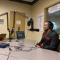 Lamont Carey (right), acting director of the Mayor's Office of Returning Citizens Affairs, discusses barriers to housing and employment for former inmates with WPFW radio host Roach Brown on Tuesday. (Sophie Kaplan/The Washington Times)