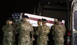 In this January 14, 2020 file photo, a U.S. Army carry team lifts a transfer case containing the remains of a soldier killed in Afghanistan, at Dover Air Force Base in Dover, Del. (AP Photo/Matt Rourke) **FILE**