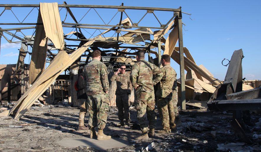 In this Monday, Jan. 13, 2020 photo, U.S. soldiers stand at the spot hit by Iranian bombing at Ain al-Asad air base, in Anbar, Iraq. Ain al-Asad air base was struck by a barrage of Iranian missiles on Wednesday, in retaliation for the U.S. drone strike that killed a top Iranian commander Gen. Qassem Soleimani. (AP Photo/Qassim Abdul-Zahra)