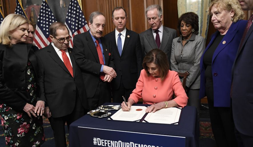 House Speaker Nancy Pelosi of Calif., signs the resolution to transmit the two articles of impeachment against President Donald Trump to the Senate for trial on Capitol Hill in Washington, Wednesday, Jan. 15, 2020. The two articles of impeachment against Trump are for abuse of power and obstruction of Congress. She is surrounded by, from left, House Oversight and Government Reform Committee Chair Rep. Carolyn Maloney, D-N.Y., Rep. Sylvia Garcia, D-Texas, House Judiciary Committee Rep. Jerrold Nadler, D-N.Y., House Foreign Affairs Committee Chairman Rep. Eliot Engel, D-N.Y., House Intelligence Committee Chairman Adam Schiff, D-Calif., House Ways and Means Committee Chairman Rep. Richard Neal, D-Mass., House Financial Services Committee Chairwoman Maxine Waters, D-Calif., Rep. Zoe Lofgren, D-Calif., and Rep. Jason Crow, D-Colorado. (AP Photo/Susan Walsh)