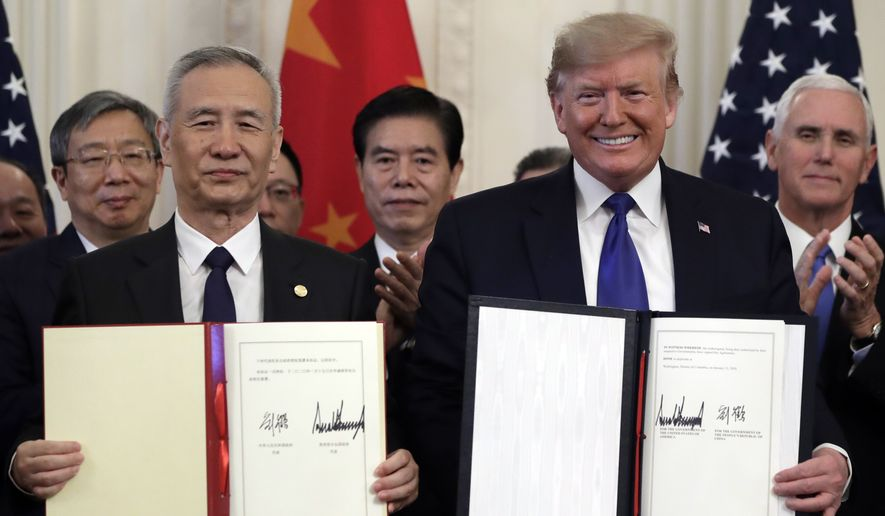 President Donald Trump signs a trade agreement with Chinese Vice Premier Liu He, in the East Room of the White House, Wednesday, Jan. 15, 2020, in Washington. (AP Photo/Evan Vucci)
