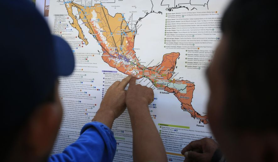 FILE - In this Nov. 9, 2018 file photo, migrants discuss their journey using a map posted inside the sports complex where thousands of migrants have been camped out for several days in Mexico City.  The United States began sending Honduran and Salvadoran asylum seekers to Guatemala in November 2019 and in Jan. 2020 said it would expand it to Mexicans. (AP Photo/Rebecca Blackwell, File)