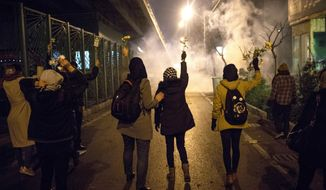 In this photograph taken Saturday, Jan. 11, 2020, protesters hold flowers as tear gas fired by police rises at a demonstration in front of Amir Kabir University in Tehran, Iran, to remember victims of a Ukrainian airplane shot down by an Iranian missile. On Monday, Jan. 13, 2020, online videos purported to show that Iranian security forces fired both live ammunition and tear gas to disperse demonstrators protesting against the Islamic Republic's initial denial that it shot down a Ukrainian jetliner. (AP Photo)