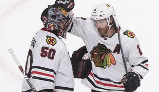 Chicago Blackhawks goaltender Corey Crawford celebrates with teammate Duncan Keith after the Blackhawks defeated the Montreal Canadiens in an NHL hockey game Wednesday, Jan. 15, 2020, in Montreal. (Graham Hughes/The Canadian Press via AP)