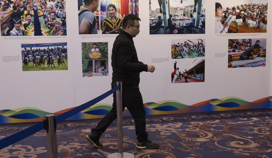 FILE - In this Dec. 11, 2019, file photo, a man walks past a display of photos from Xinjiang during a forum on human rights in Beijing. China has blasted a report from Human Rights Watch that accused it of constructing a surveillance state at home while seeking to silence critics abroad. (AP Photo/Ng Han Guan, File)