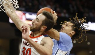 RETRANSMISSION TO CORRECT CITY - Virginia forward Jay Huff (30) and North Carolina guard Cole Anthony, right, collide under the basket during the first half of an NCAA college basketball game in Charlottesville, Va., Sunday, Dec. 8, 2019. (AP Photo/Steve Helber) **FILE**