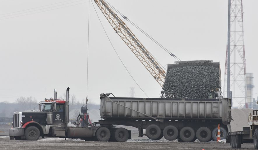 Material is loaded into a gravel-train semi at Detroit Bulk Storage, a sand and gravel storage yard in Detroit.  (Todd McInturf/Detroit News via AP)
