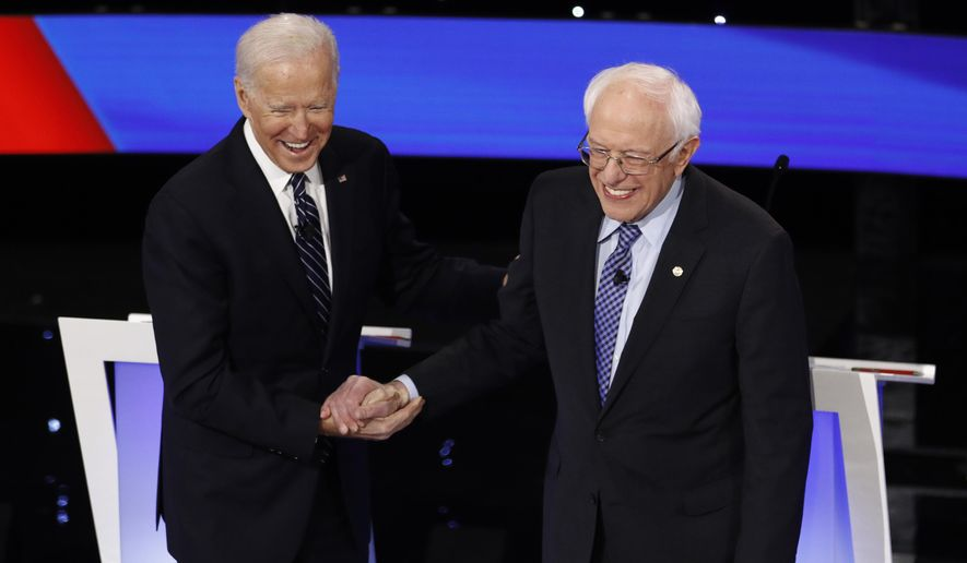 Democratic presidential candidates former Vice President Joe Biden, left, and Sen. Bernie Sanders, I-Vt., greet each other Tuesday, Jan. 14, 2020, before a Democratic presidential primary debate hosted by CNN and the Des Moines Register in Des Moines, Iowa. (AP Photo/Patrick Semansky) ** FILE **