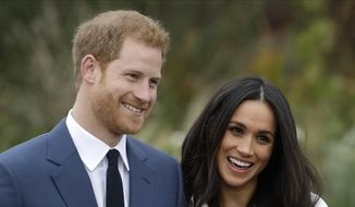 In this Monday, Nov. 27, 2017, file photo, Britain's Prince Harry and his then-fiancee Meghan Markle pose for photographers during a photocall in the grounds of Kensington Palace in London. (AP Photo/Matt Dunham, File)