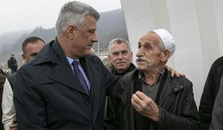 Kosovo president Hashim Thaci, comforts Hafiz Musafaj, during his visit to the Recak memorial, in the village of Recak on Tuesday, Dec. 10, 2019, where he called on Serbia to apologize for the genocide on his country as the first step toward a peaceful future relationship. Thaci, a former commander of the Kosovo Liberation Army independence fighters, or KLA, said that during its genocide campaign in 1998-1999 Serbia committed some 400 massacres, killing about 13,000 civilians, including 1,300 children. Some 1,650 are still unaccounted for. (AP Photo/Visar Kryeziu)