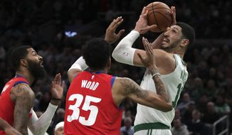 Boston Celtics center Enes Kanter, right, is pressured by Detroit Pistons forwards Christian Wood (35) and Markieff Morris, left, during the first half of an NBA basketball game in Boston, Wednesday, Jan. 15, 2020. (AP Photo/Charles Krupa)