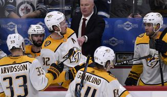 Nashville Predators head coach John Hynes, top center, instructs players during third-period NHL hockey game action against the Winnipeg Jets in Winnipeg, Manitoba, Sunday Jan. 12, 2020. (Fred Greenslade/The Canadian Press via AP)
