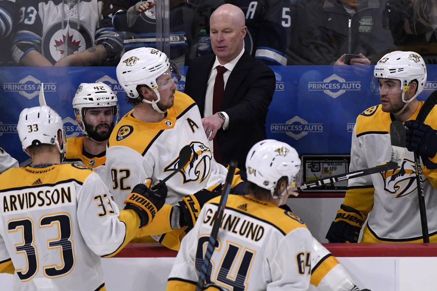 Nashville Predators head coach John Hynes, top center, instructs players during third-period NHL hockey game action against the Winnipeg Jets in Winnipeg, Manitoba, Sunday Jan. 12, 2020. (Fred Greenslade/The Canadian Press via AP)