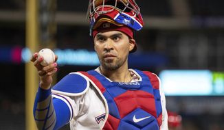 FILE - In this Aug. 16, 2018, file photo, Texas Rangers catcher Robinson Chirinos offers to toss a ball to a fan during a baseball game against the Los Angeles Angels, in Arlington, Texas. Robinson Chirinos and the Texas Rangers were close Wednesday, Jan. 8, 2020, to a $6.5 million, one-year contract to reunite after the veteran catcher spent a season with the AL West rival Houston Astros. A person familiar with the deal said the agreement was contingent on a successful physical. The person spoke to The Associated Press on condition of anonymity because there had been no official announcement. (AP Photo/Jeffrey McWhorter, File)