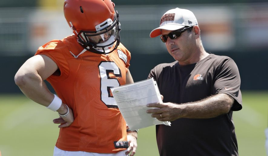 FILE - In this July 26, 2018, file photo, Cleveland Browns quarterbacks coach Ken Zampese, right, talks with quarterback Baker Mayfield at the NFL football team's training camp facility, in Berea, Ohio. The Washington Redskins have hired Ken Zampese as their quarterbacks coach on Ron Rivera's new-look staff. The team revealed Rivera's full staff on Wednesday, Jan. 15, 2020. (AP Photo/Tony Dejak, File)