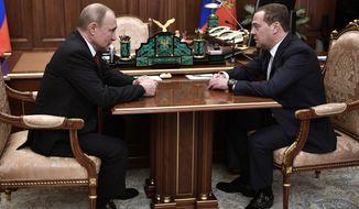Russian President Vladimir Putin, left, listens to Russian Prime Minister Dmitry Medvedev during their meeting in the Kremlin in Moscow, Russia, Wednesday, Jan. 15, 2020. (Alexei Nikolsky, Sputnik, Kremlin Pool Photo via AP)
