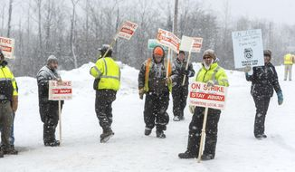 Falling snow covers Teamsters Local 320 members as they picket in front of the St. Louis County MN garage in Virginia Minn., Wednesday January 15, 2020. The St. Louis County heavy equipment and snow plow drivers went on strike Wednesday morning. (Mark Sauer/The Mesabi Daily News via AP)