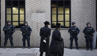 FILE - In this Dec. 11, 2019 file photo, Orthodox Jewish men pass New York City police guarding a Brooklyn synagogue prior to a funeral for Mosche Deutsch, a rabbinical student from Brooklyn who was killed in a shooting at a Jersey City, N.J. market. On Wednesday, Jan. 15, 2019, a group of security experts recommended that Jewish congregations opting to deploy armed security personnel in the wake of deadly attacks on synagogues should — if possible -- use uniformed law enforcement officers rather than private guards or volunteers from the community. (AP Photo/Mark Lennihan, File)