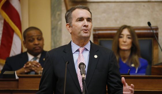 In this Jan. 8, 2020, file photo, Virginia Gov. Ralph Northam, center, gestures as he delivers his State of the Commonwealth address as House Speaker Eileen Filler-Corn, D-Fairfax, right, and Lt. Gov. Justin Fairfax, left, listen before a joint session of the Virginia Assembly at the state Capitol in Richmond, Va. (AP Photo/Steve Helber, File) ** FILE **
