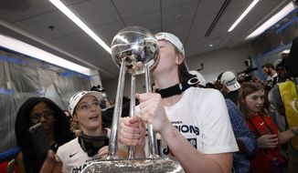 In this Oct. 10, 2019, file photo, Washington Mystics center Emma Meesseman kisses the trophy in the locker room after Game 5 of basketball's WNBA Finals against the Connecticut Sun in Washington. Washington was so bad for so long in the major professional sports but maybe soon it will be said that D.C. stands for District of Champions.  (AP Photo/Alex Brandon, File) **FILE**