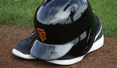 A San Francisco Giants player is reflected in a batting helmet during practice before the spring baseball season in Scottsdale, Ariz., Thursday, Feb. 18, 2016. (AP Photo/Chris Carlson) **FILE**