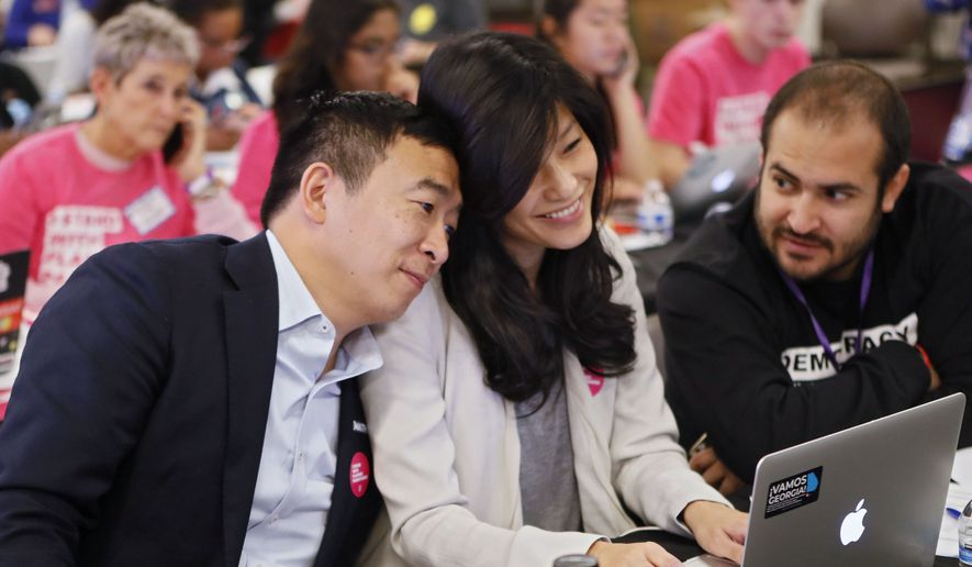 In this Nov. 21, 2019, file photo, Democratic presidential candidate former technology executive Andrew Yang, leans on his wife with his wife Evelyn, as they join in at a Fair Fight phone bank at Ebenezer Baptist Church in Atlanta. The wife of Democratic presidential candidate Andrew Yang says she was sexually assaulted by her OB-GYN while she was pregnant with the couple's first child. (Bob Andres/Atlanta Journal-Constitution via AP)