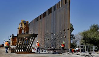 In this Sept. 10, 2019, file photo, government contractors erect a section of Pentagon-funded border wall along the Colorado River in Yuma, Ariz. (AP Photo/Matt York) ** FILE **