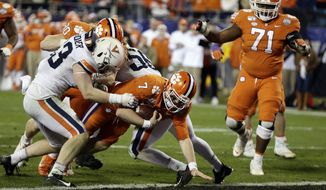 Clemson quarterback Chase Brice (7) scores a touchdown against Virginia during the second half of the Atlantic Coast Conference championship NCAA college football game in Charlotte, N.C., Saturday, Dec. 7, 2019. Clemson won 62-17. (AP Photo/Gerry Broome)