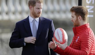 Britain's Prince Harry listens to Rugby League World Cup 2021 (RLWC2021) ambassador James Simpson in the gardens at Buckingham Palace in London, Thursday, Jan. 16, 2020. Prince Harry, the Duke of Sussex will host the Rugby League World Cup 2021 draw at Buckingham Palace, prior to the draw, The Duke met with representatives from all 21 nations taking part in the tournament, as well as watching children from a local school play rugby league in the Buckingham Palace gardens. (AP Photo/Kirsty Wigglesworth)