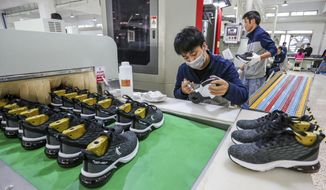 In this Jan. 3, 2020, photo, workers make sneakers in a factory in Jinjiang city in southeastern China's Fujian province. China's economic growth sank to a new multi-decade low of 6.1% in 2019 as consumer demand weakened and Beijing fought a trade war with Washington. Government data Friday, Jan. 17, showed growth was down from 2018's 6.6%, already the lowest since 1990. Economic growth in the three months ending in December held steady at the previous quarter's level of 6%. (Chinatopix Via AP)