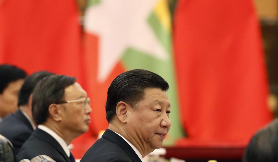 FILE - In this April 10 2017, file photo, Chinese President Xi Jinping, center, accompanied by Chinese State Councilor Yang Jiechi, left, attends a meeting with Myanmar's President Htin Kyaw at the Great Hall of the People in Beijing. Foreign Ministry spokeswoman Hua Chunying announced Friday, Jan. 10, 2020, that Xi would visit Myanmar on Jan. 17-18.  (Yohei Kanasashi/Pool Photo via AP, File)