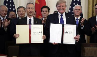 """FILE - In this Wednesday, Jan. 15, 2020, file photo, U.S. President Donald Trump, right, signs a trade agreement with Chinese Vice Premier Liu He, in the East Room of the White House, in Washington. China's government welcomed an interim trade deal with Washington and said Thursday the two sides need to address each other's """"core concerns."""" (AP Photo/Evan Vucci, File)"""