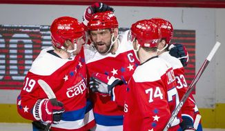 Washington Capitals left wing Alex Ovechkin (8), from Russia, is congratulated by center Nicklas Backstrom (19) from Sweden, defenseman John Carlson (74), and defenseman Radko Gudas (33), from Czech Republic, after scoring during the first period of an NHL hockey game against the New Jersey Devils, Thursday, Jan. 16, 2020, in Washington. (AP Photo/Al Drago)