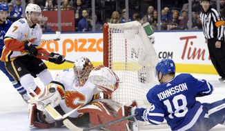 Calgary Flames goaltender David Rittich (33) makes a save against Toronto Maple Leafs left wing Andreas Johnsson (18) during the second period of an NHL hockey game Thursday, Jan. 16, 2020, in Toronto. (Nathan Denette/The Canadian Press via AP)