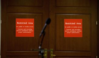 FILE - In this Nov. 15, 2019, file photo a microphone stands at the entrance to a secure area during a closed-door interview with David Holmes, a career diplomat and the political counselor at the U.S. Embassy in Kyiv, Ukraine, on Capitol Hill in Washington. The Labor Department will begin restricting news organizations' use of economic data by barring computers from the rooms where reporters receive such data before its public release, department officials announced Thursday, Jan. 16, 2020. (AP Photo/Jose Luis Magana, File)