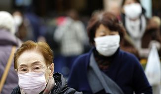 Pedestrian wear protective masks as they walk on a shopping district in Tokyo Thursday, Jan. 16, 2020. Japan's government said Thursday a man treated for pneumonia after returning from China has tested positive for the new coronavirus identified as a possible cause of an outbreak in the Chinese city of Wuhan.(AP Photo/Eugene Hoshiko)