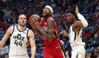 New Orleans Pelicans forward Brandon Ingram drives to the basket between Utah Jazz forward Bojan Bogdanovic (44) and guard Donovan Mitchell during the first half of an NBA basketball game in New Orleans, Thursday, Jan. 16, 2020. (AP Photo/Gerald Herbert)