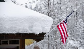 Snow covers the roof of Steven's Pizza in Skykomish, Wash., along Highway 2, Wednesday, Jan. 15, 2020, in Skykomish, Wash. Volunteers brought food and supplies here for local Skykomish residents stranded without power or access to food. (Mike Siegel/The Seattle Times via AP)