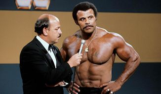 """In this undated photo provided by WWE, Inc., """"Mean"""" Gene Okerlund interviews Rocky """"Soul Man"""" Johnson. Johnson, a WWE Hall of Fame wrestler who became better known as the father of actor Dwayne """"The Rock"""" Johnson, died Wednesday, Jan. 15, 2020. He was 75. (WWE, Inc. via AP)"""