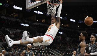 Atlanta Hawks forward John Collins (20) scores over San Antonio Spurs guard DeMar DeRozan, second from right, during the first half of an NBA basketball game in San Antonio, Friday, Jan. 17, 2020. (AP Photo/Eric Gay)