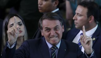Brazil's President Jair Bolsonaro gestures during an event with young Venezuelan migrants at the Planalto Presidential Palace in Brasilia, Brazil, Thursday, Jan. 16, 2020. According to the UNHCR there are around 180,000 Venezuelan refugees and migrants in the country, many of them arrived crossing the border  in the northern state of Roraima. (AP Photo/Eraldo Peres)