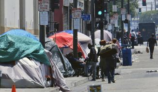 FILE - In this May 30, 2019 file photo, tents housing homeless line a street in downtown Los Angeles. Nonprofit health care system Kaiser Permanente today announced it will be the first private sector contributor to Newsom's newly announced fund to combat homelessness in the state, committing $25 million to the effort. (AP Photo/Richard Vogel, File)