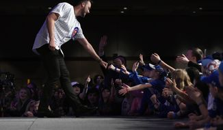 Chicago Cubs' Kris Bryant, left, fist-bumps fans after being announced during the baseball team's convention, Friday, Jan. 17, 2020, in Chicago. (AP Photo/Paul Beaty)