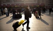 A traveler wears a facemask as he walks in front of the Beijing Railway Station in Beijing, Friday, Jan. 17, 2020. A second person has died from a new form of coronavirus in central China, health authorities said late Thursday. (AP Photo/Mark Schiefelbein)